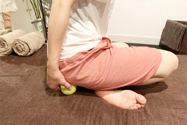 おしり(臀部)と床の間にテニスボールを挟む